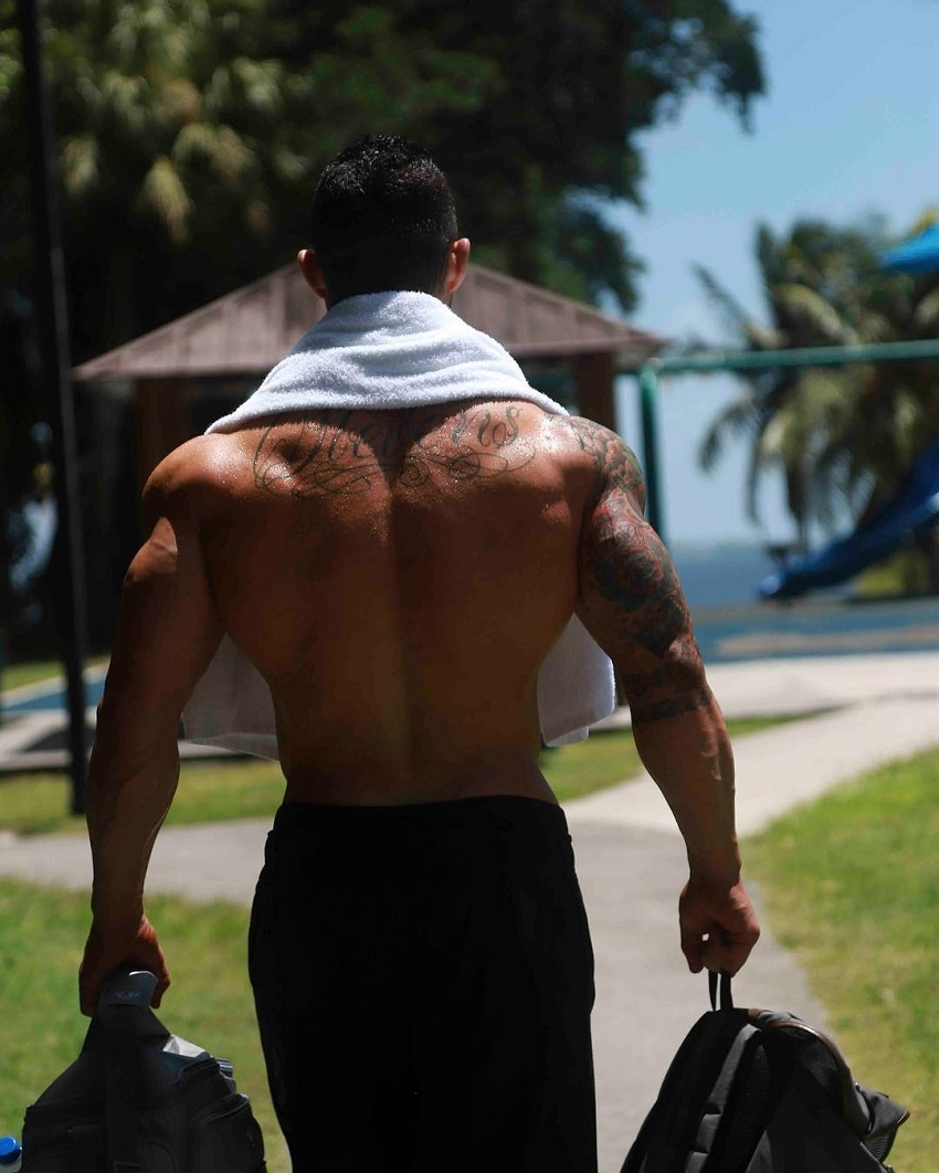 Jase Stevens walking shirtless down the road carrying bags, looking swole and ripped
