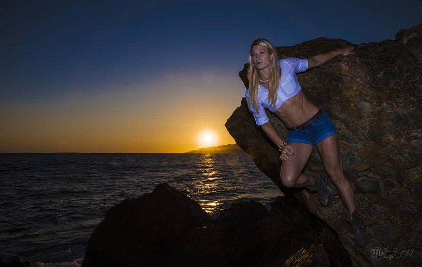 Jessie Graff posing by the rock during a sunset