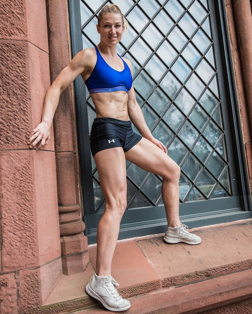Jessie Graff standing by a building window looking fit
