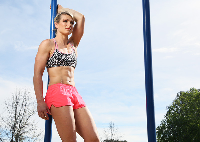 Jessie Graff posing outdoors in the sun, resting by a pole, looking lean and fit