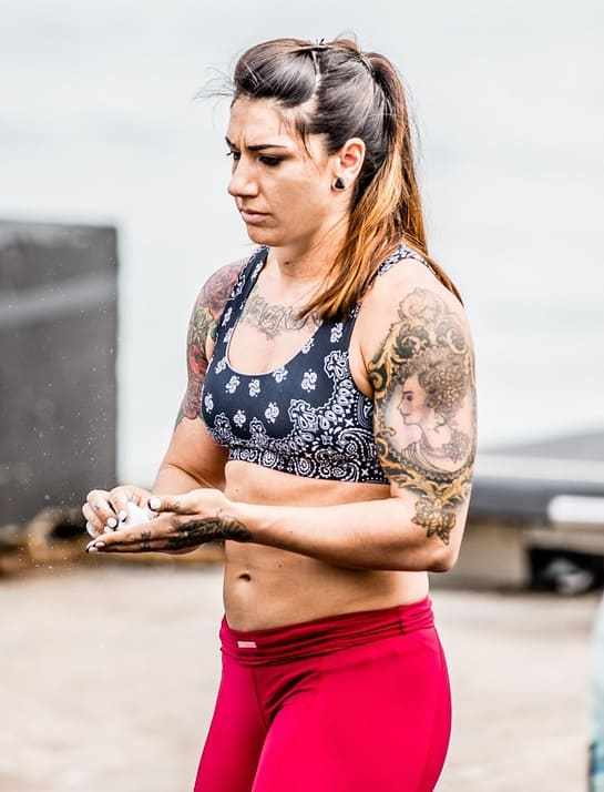 Kat Leone rubbing chalk into her hands during a crossfit event
