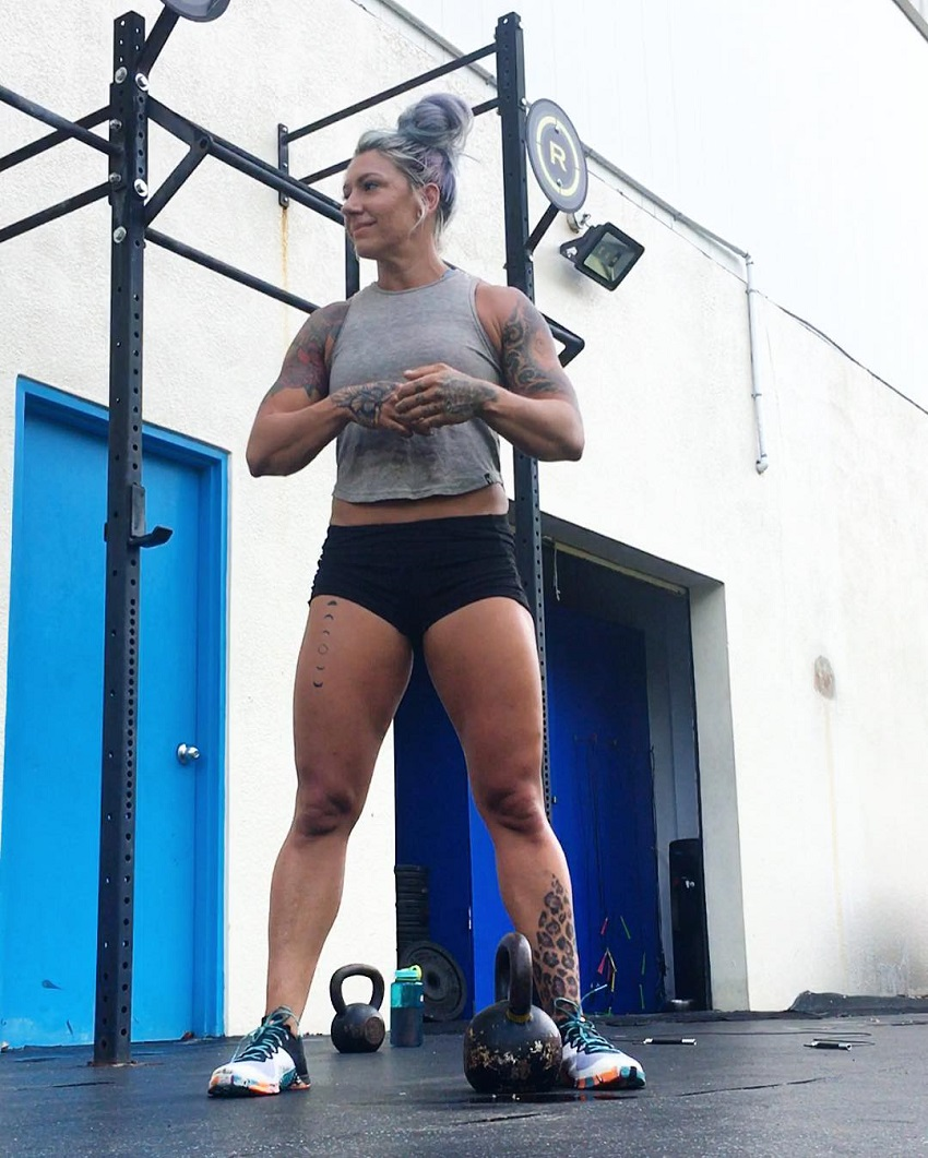 Kat Leone standing next to a kettlebell in a crossfit gym looking fit