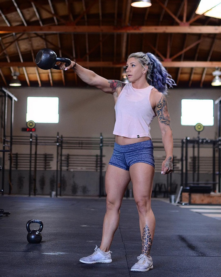 Kat Leone performing kettlebell swings in a crossfit gym