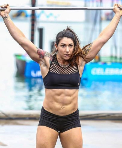 Kat Leone lifting heavy barbell overhead during a crossfit contest