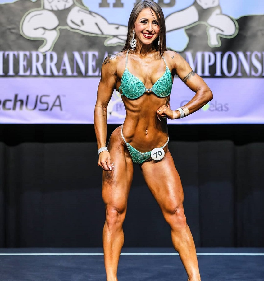 Olena Starodubets posing and smiling on the wellness IFBB stage