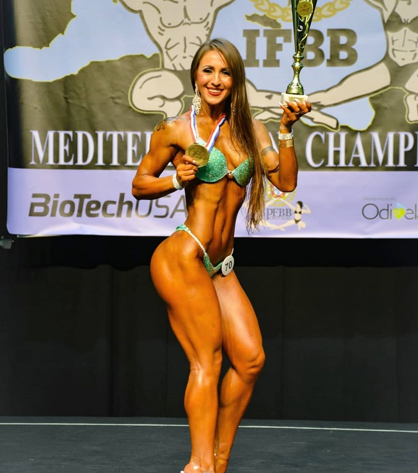 Olena Starodubets posing on the stage with a trophy and a medal in her hands