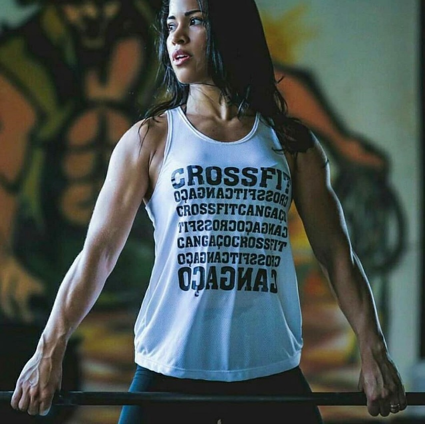 Rosana Ollyver posing in a white crossfit t-shirt holding a barbell