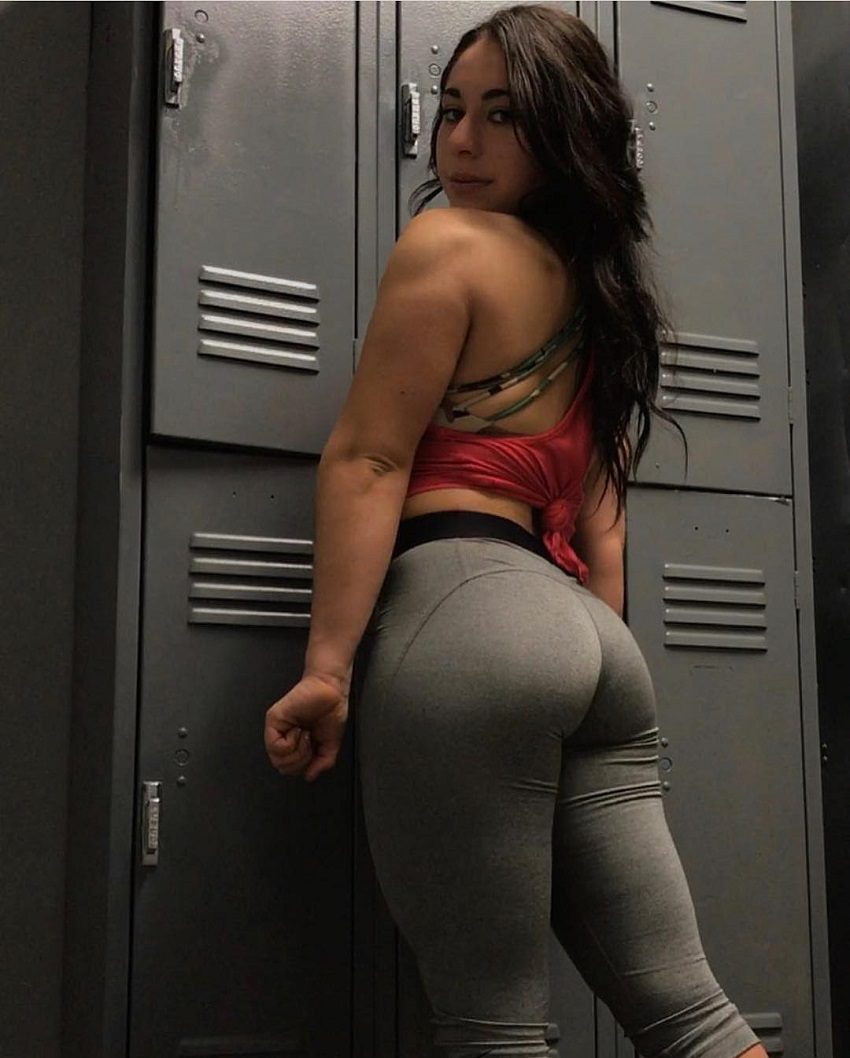 Samyra Zane Abweh flexing her triceps and glutes in grey leggings in a gym locker room
