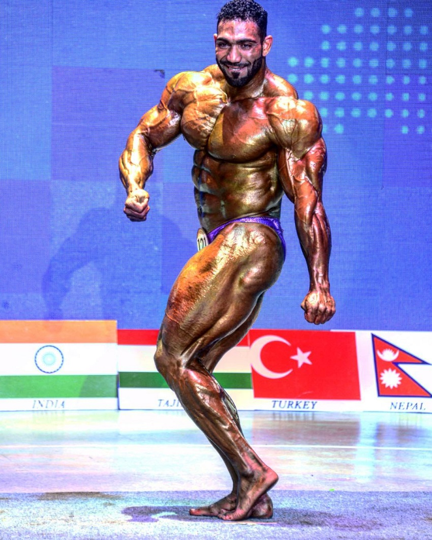 Yasin Qaderi doing a side tricep flex in front of a judges in a bodybuilding contest