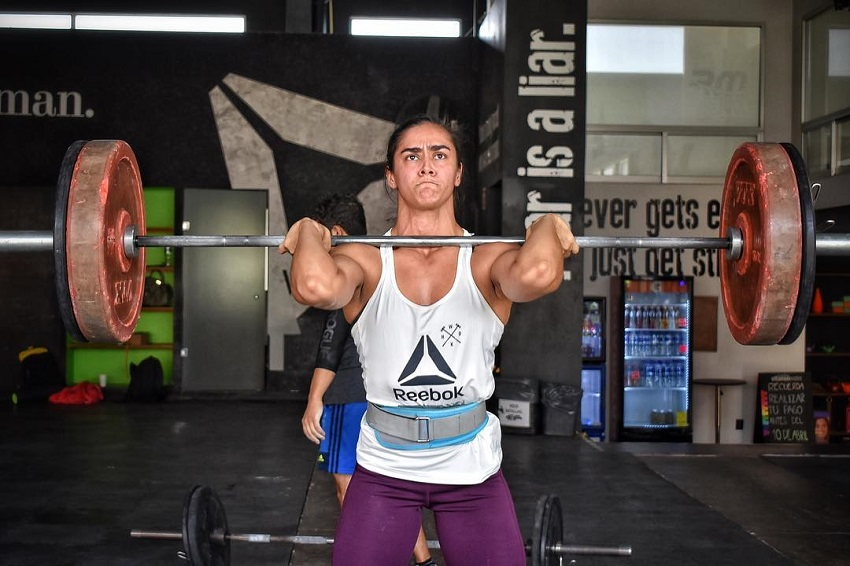 Yazmin Arroyo Loaiza doing a heavy overhead barbell press looking mentally focused and strong