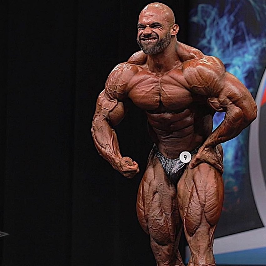 Alexis Rivera Rolon doing a most muscular pose on the bodybuilding stage, looking insanely ripped
