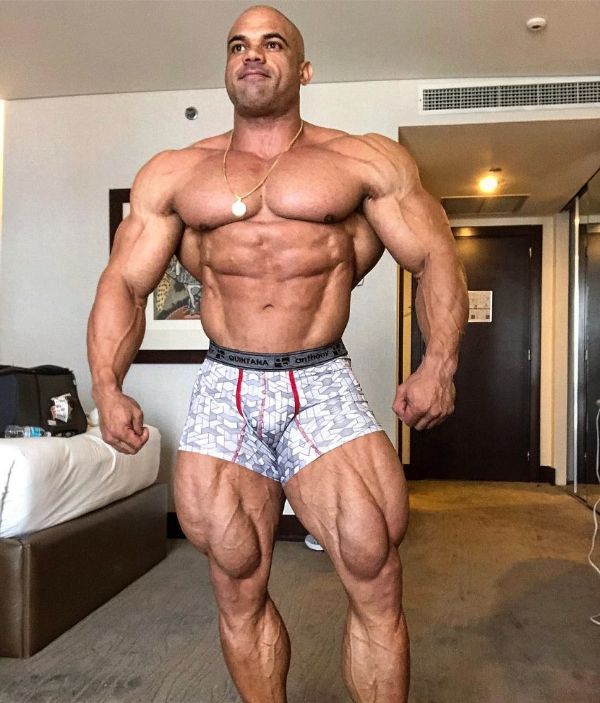 Alexis Rivera Rolon posing shirtless in his apartment, looking huge and ripped