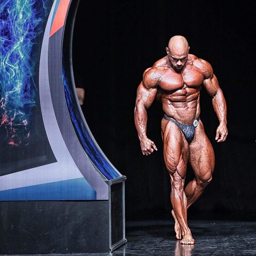 Alexis Rivera Rolon walking onto the bodybuilding stage, looking ripped and huge