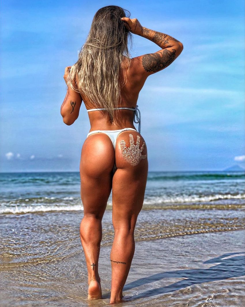 Aline Antiqueira standing on the beach showing off her curvy glutes