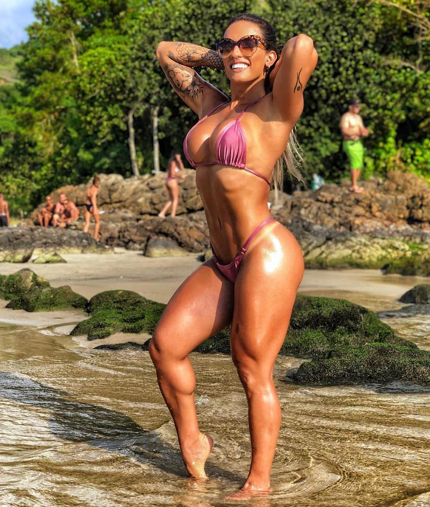 Aline Antiqueira standing in shallow waters soaking up the sun looking fit and lean
