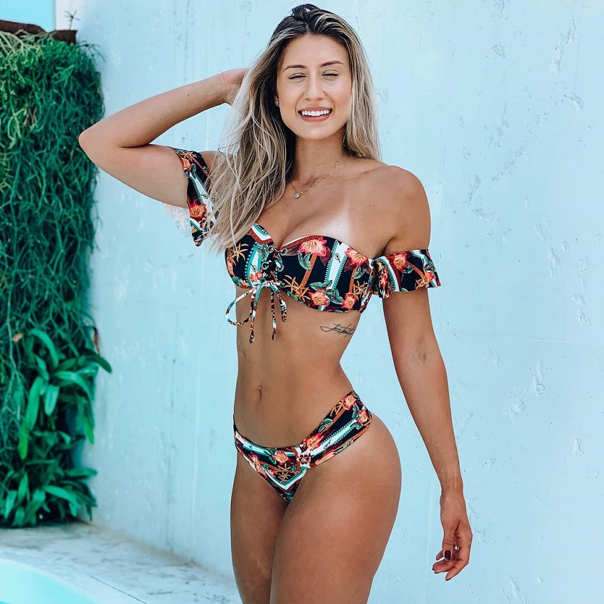 Aline Maretoposing for a picture in an exotic swimsuit looking fit