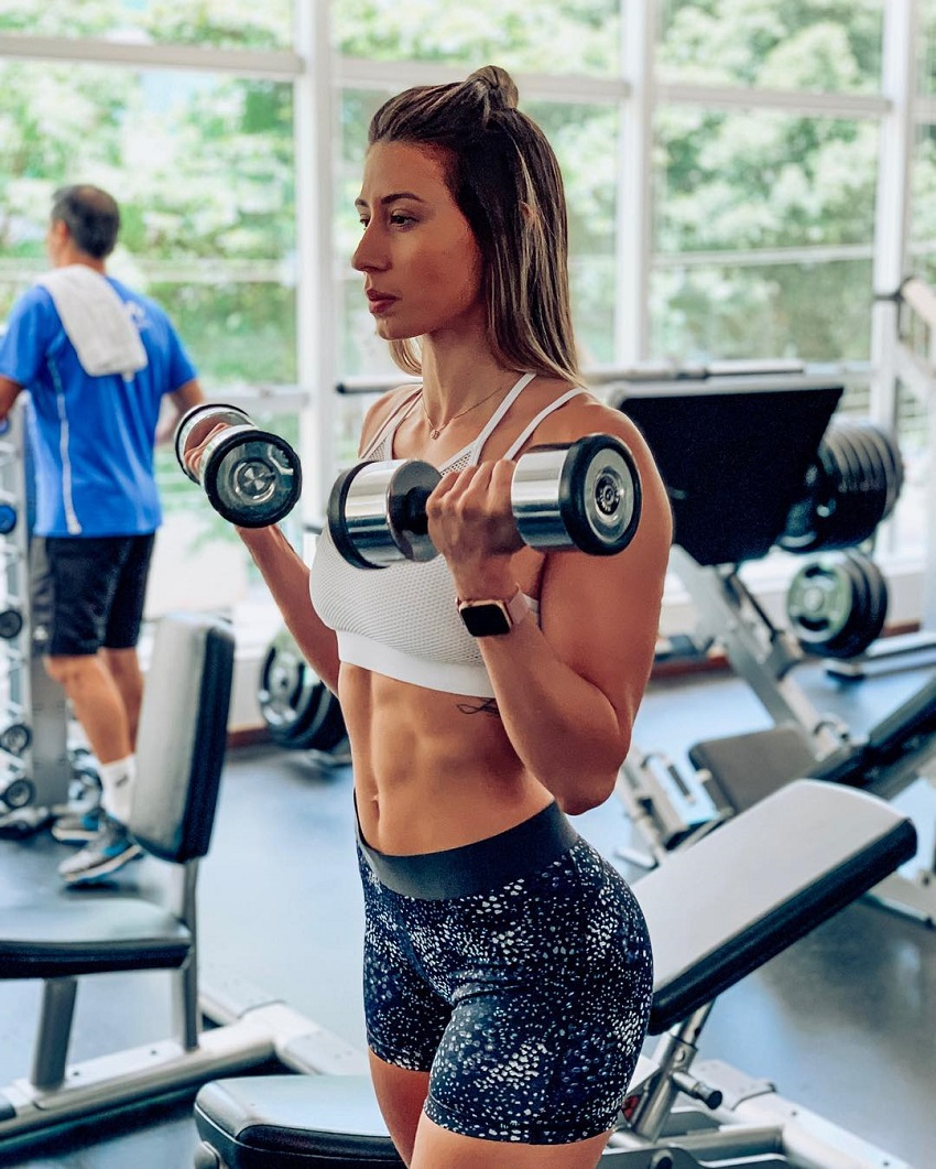 Aline Mareto curling some light dumbbells in a gym