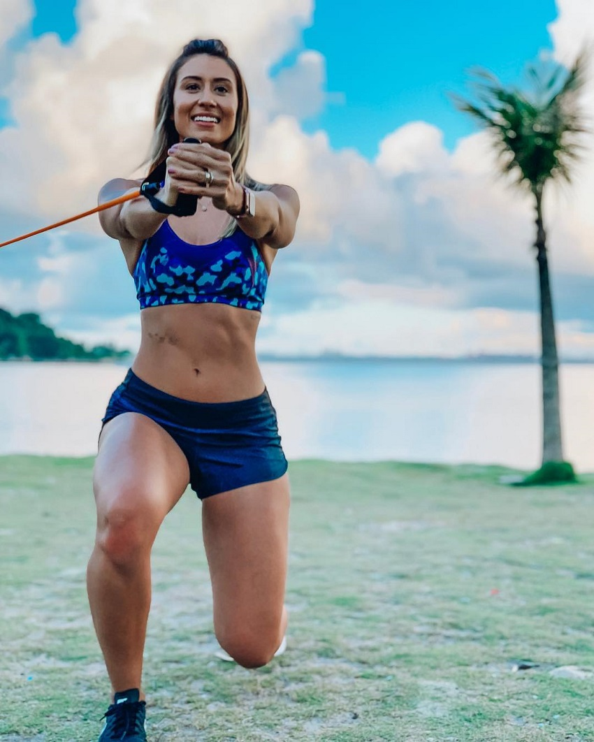 Aline Mareto training with resistance bands on a beach