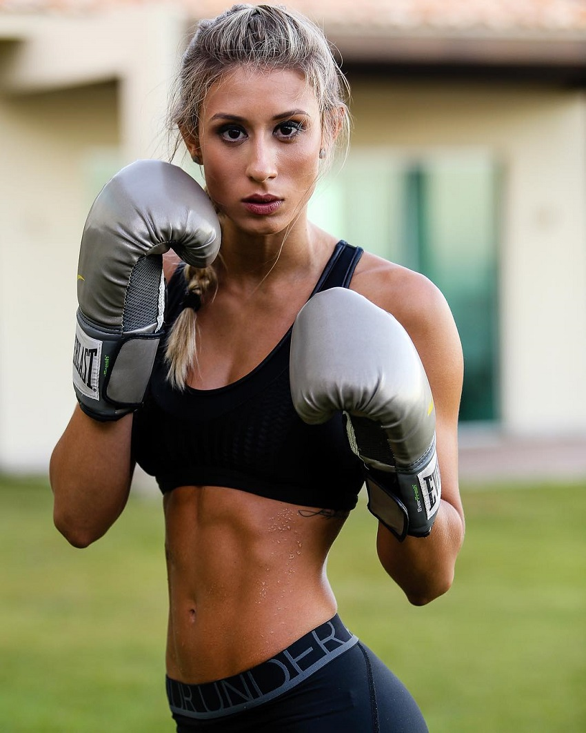 Aline Mareto posing for a picture in a boxing stance with boxing gloves on