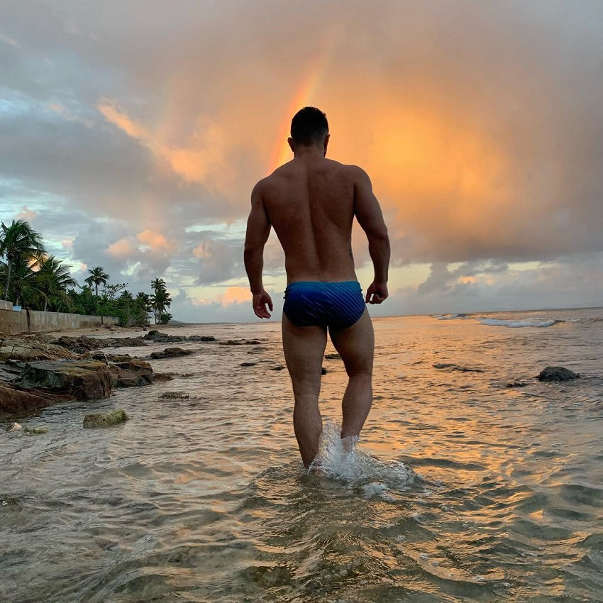 Bremen Menelli walking in shallow waters by the sea during a twilight looking fit