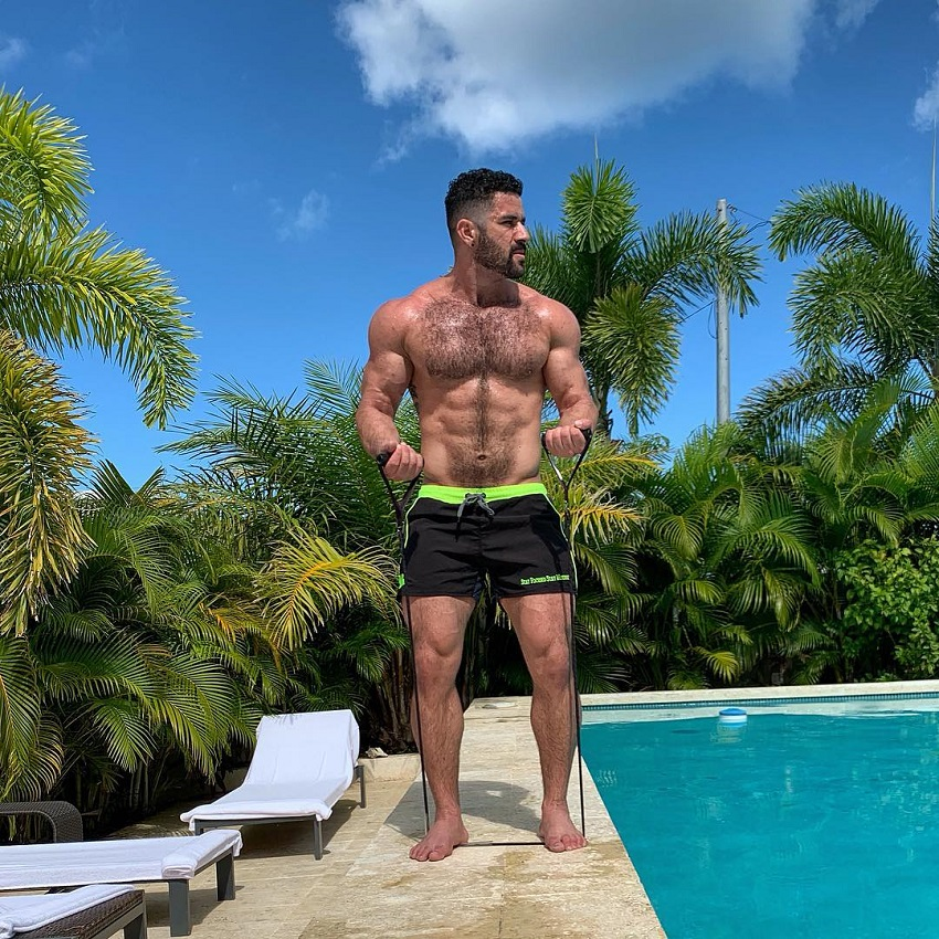 Bremen Menelli training shirtless with resistance bands by a pool