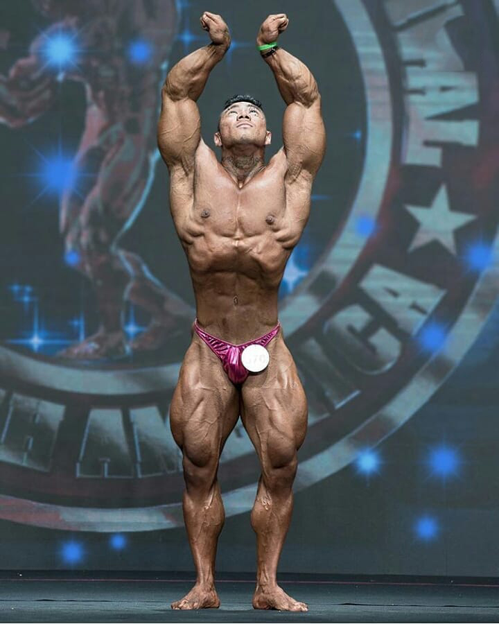 Caio Eiji Sirahata performing a posedown on a bodybuilding stage looking ripped