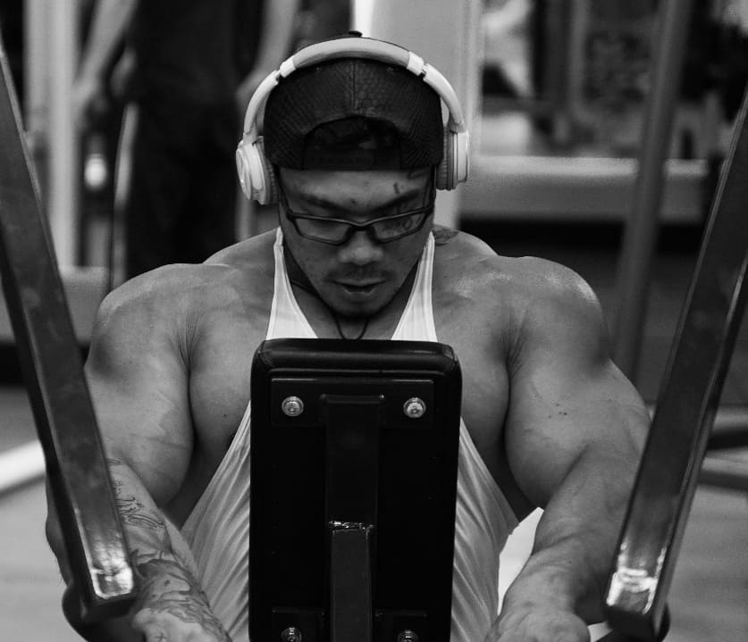 Caio Eiji Sirahata exercising his chest on a machine in a gym