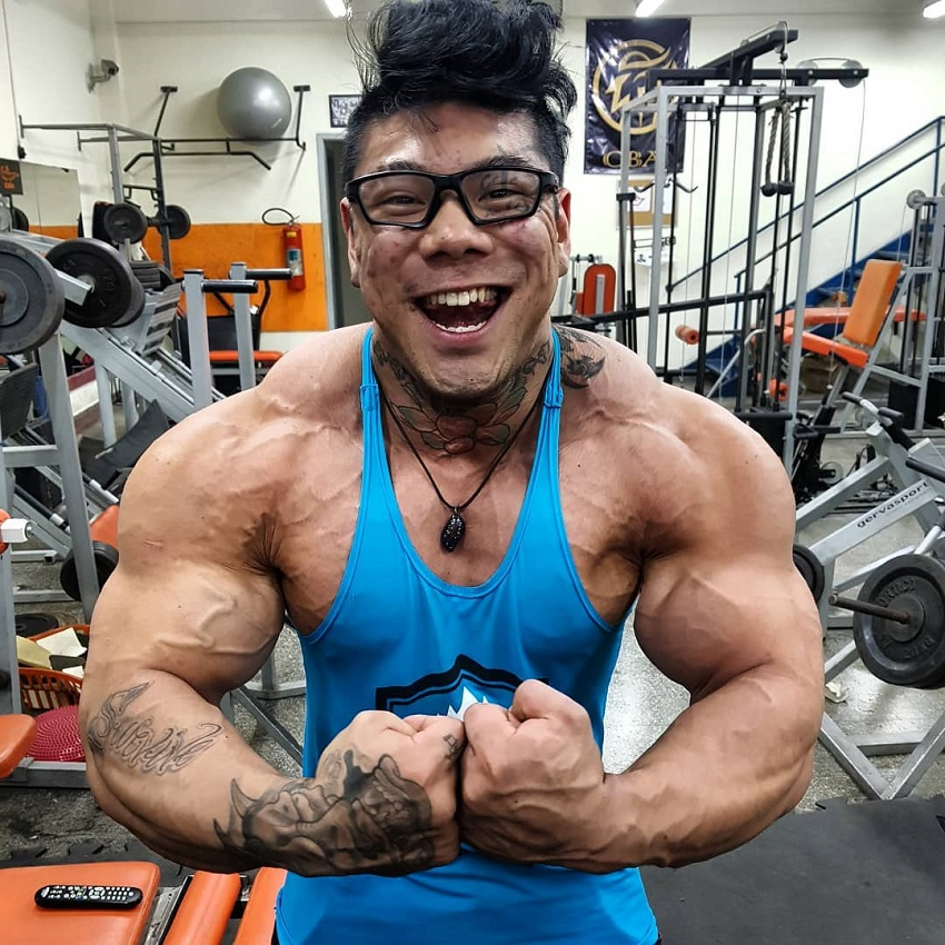 Caio Eiji Sirahata flexing for the camera, wearing a blue tank top, standing in front of cardio machines in the gym