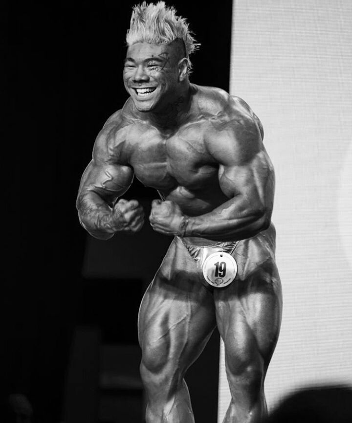 Caio Eiji Sirahata performing a most muscular pose on the bodybuilding stage