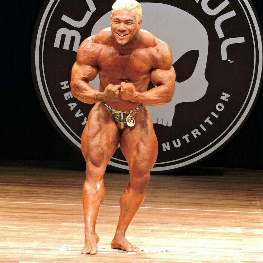 Caio Eiji Sirahata flexing on the bodybuilding stage