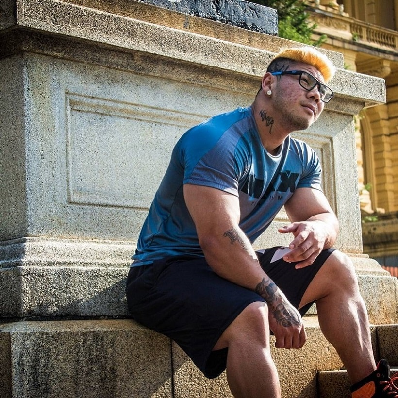 Caio Eiji Sirahata sitting near a statue looking strong and well-built