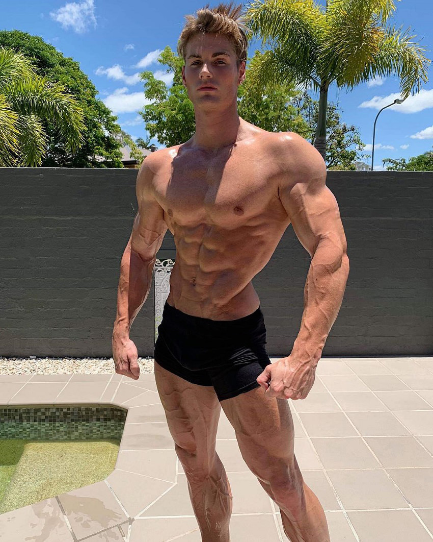 Carlton Loth posing shirtless in his backyard looking ripped and fit