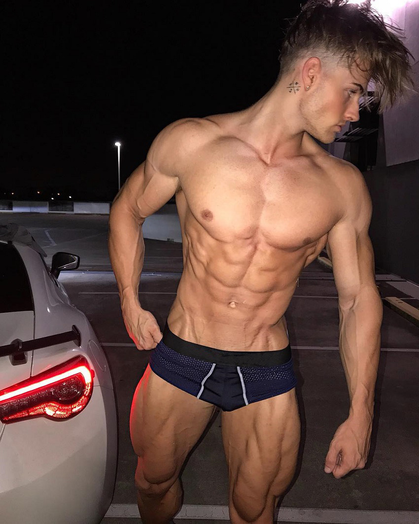Carlton Loth posing shirtless next to a white car during the night