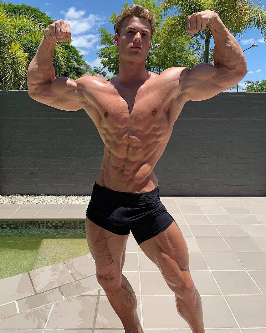 Carlton Loth doing a shirtless front double biceps pose for the photo