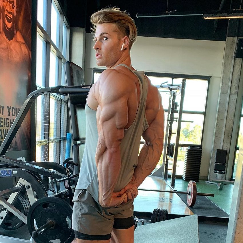 Carlton Loth flexing his ripped and bulging triceps in a gym