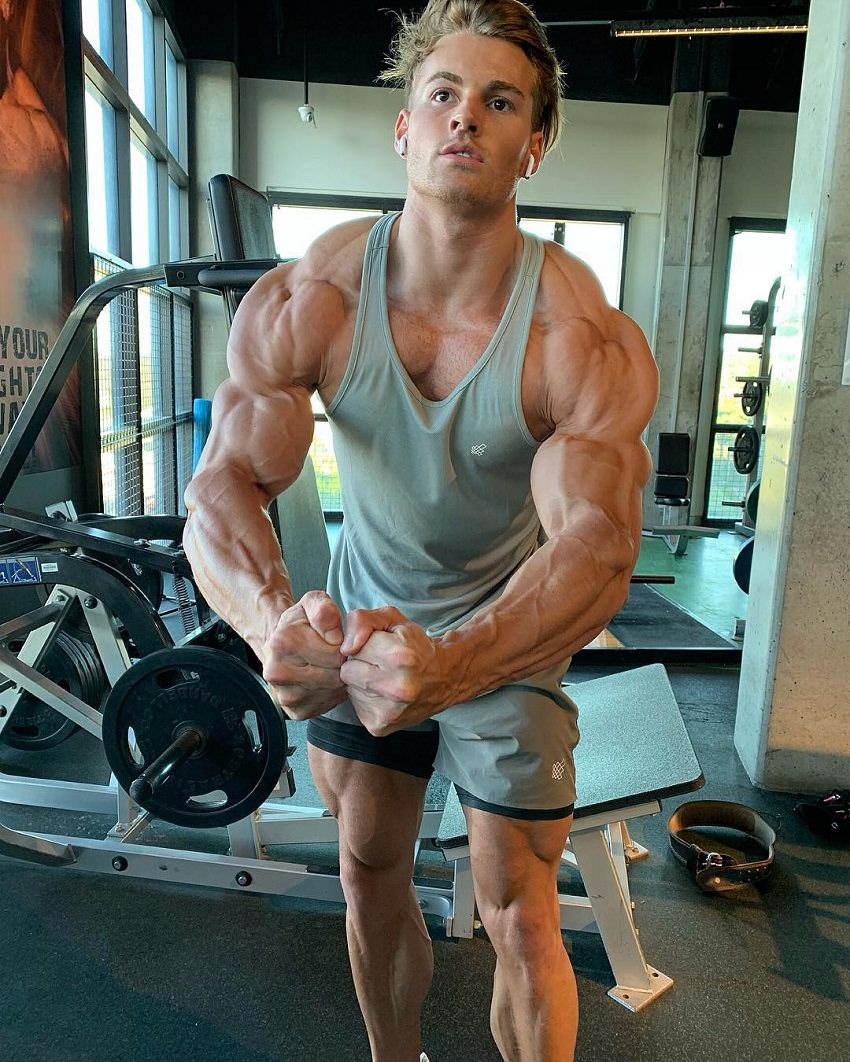 Carlton Loth flexing his muscles in a greyish tank top in the gym