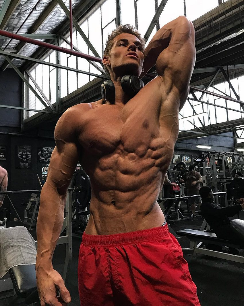 Carlton Loth posing shirtless in red shorts in the gym looking ripped and aesthetic