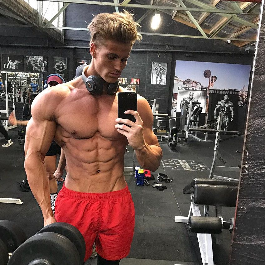 Carlton Loth taking a shirtless selfie in the gym looking ripped