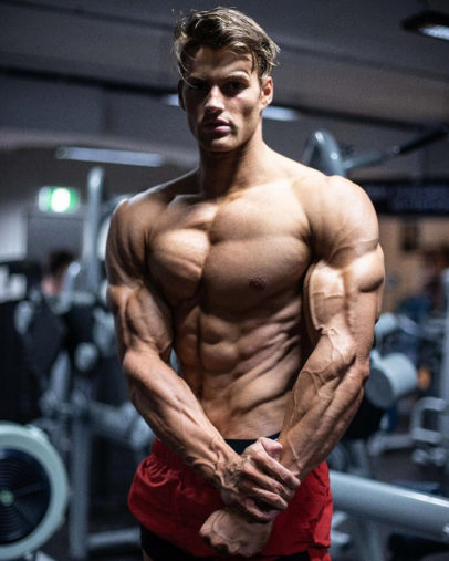 Carlton Loth flexing shirtless in the gym