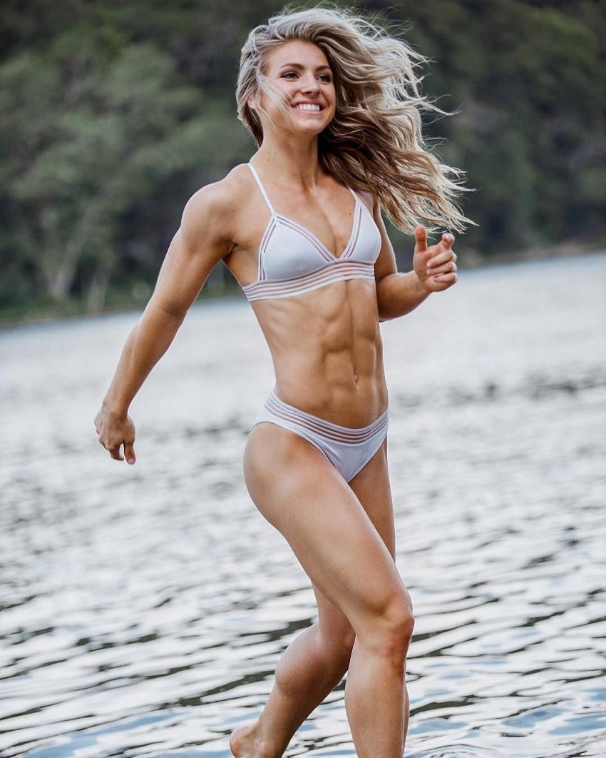 Claire P Thomas running by the lake in her bathing suit, smiling, looking ripped