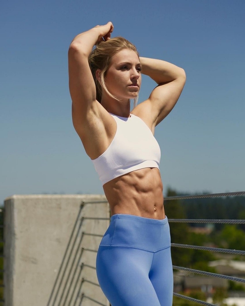 Claire P Thomas tying her heair outdoors on a sunny day, her abs looking ripped