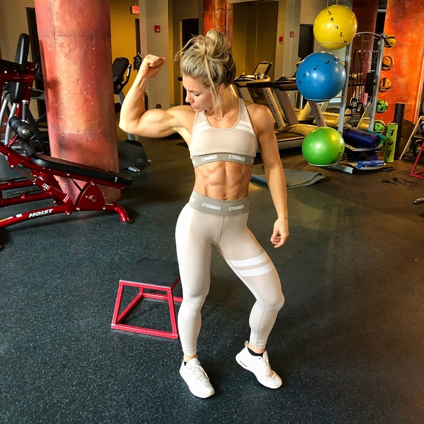 Claire P Thomas flexing her bulging biceps in the gym