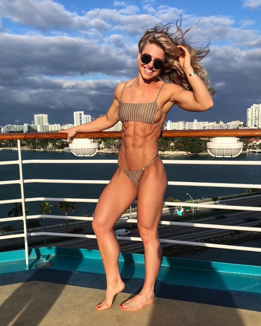 Claire P Thomas standing on the bridge near sea, smiling and posing in a bikini, looking fit and lean