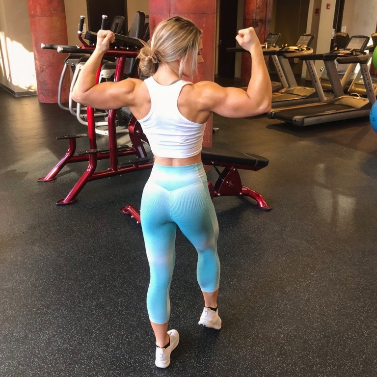 Claire P Thomas doing a back double biceps flex in the gym