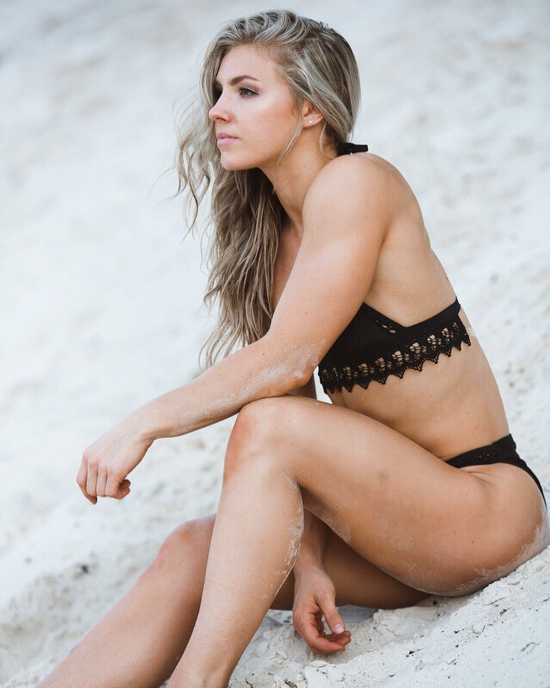 Claire P Thomas sitting on a rock in her black bathing suit, looking fit and toned