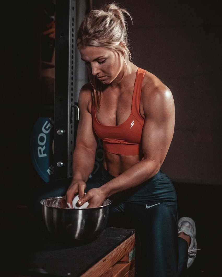 Claire P Thomas rubbing white chalk between her hands, preparing to do a heavy lift in the gym, looking strong and muscular
