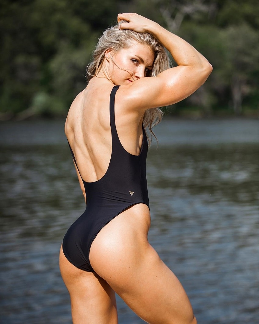Claire P Thomas showing off her glutes and back muscles in a photo shoot, wearing a black swimsuit