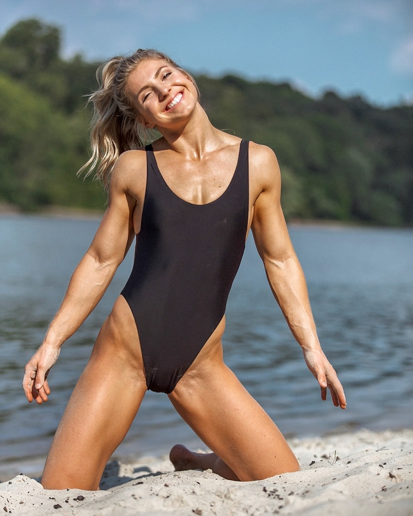 Claire P Thomas posing on a beach in a black swimsuit looking ripped and aesthetic