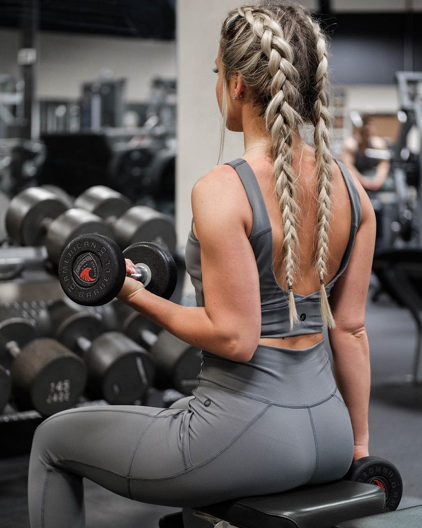 Picture of Cristina Capron from the back, doing seated biceps curls in a gym