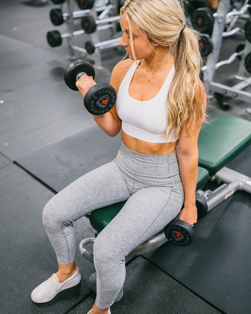 Cristina Capron doing seated biceps curls in a gym